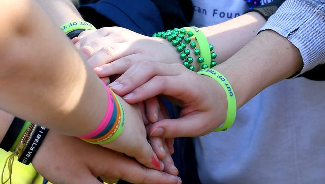 Members of Riverheads High School's Key Club put their hands together to show both unity and the bracelets they wear. The third annual Greater Augusta Out of the Darkness Walk was held at Gypsy Hill Park on Saturday, Oct. 21, 2017. The event brought together people affected by suicide and promoted awareness to suicide prevention.
