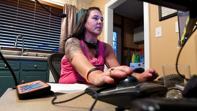 Cortney Small works at her computer on Nov. 12, 2017.  The system and workspace have been tailored to help with her work, despite her loss of several fingers and legs below the knees.