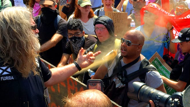 A white nationalist gives a counter protester the finger as another fires pepper spray at the man and those around him. Saturday's planned rally at Emancipation Park started early with fighting and devolved into bottle-throwing clashes between racist alt-right demonstrators who organized the event, white nationalists, neo-Nazis and counter protesters in Charlottesville.  Later during a counter march along Water Street near the Mall, a driver drove his car into a group of protesters, killing one.
