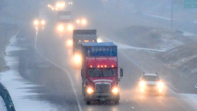 Snow falls as traffic flows south on Interstate 81 near the Interstate 64 interchange at Staunton on Wednesday, Jan. 17, 2018.
