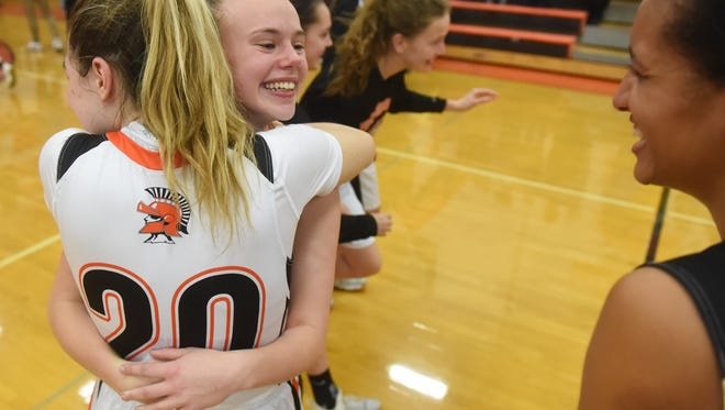 York Suburban's Kennedy Mckee is all smiles as she embraces teammate Katherine Mooney following the Trojans' 43-40 victory over Eastern York in the first round of the the Class 4A tournament on Tuesday, Feb. 20, 2018.