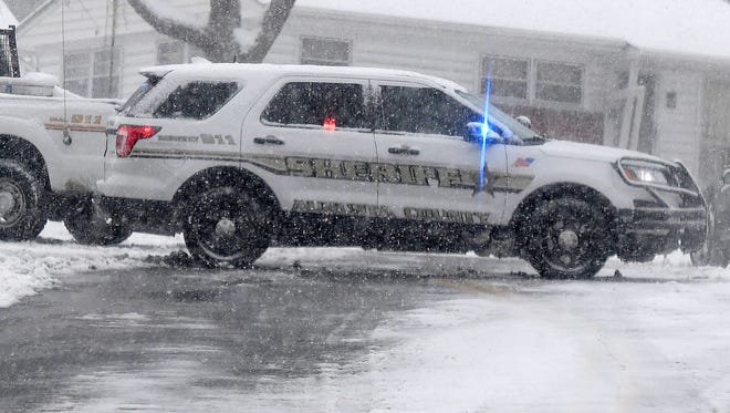 Snow falls as vehicles with the Augusta County Sheriff's Office partially block Frontier Drive at Barterbrook Road in Staunton on Monday, March 12, 2018.