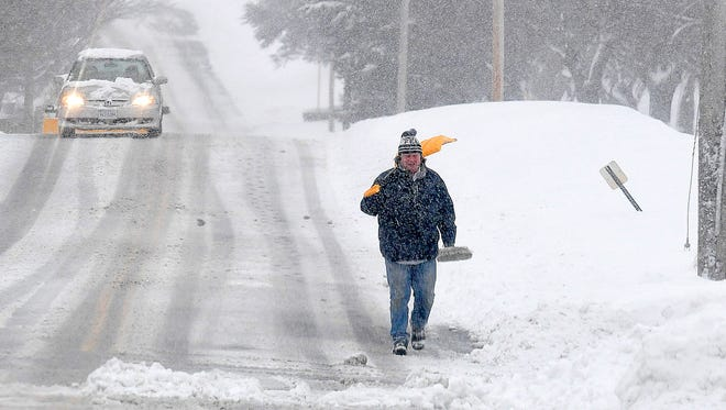 A man walks along Barterbrook Road with snow shovel slung over one shoulder during a spring snow storm on Wednesday, March 21, 2018.