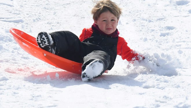 A young sledder digs into the snow with one hand while riding his sled down a snow covered hill on the campus of Mary Baldwin University in Staunton on Thursday, March 22, 2018.