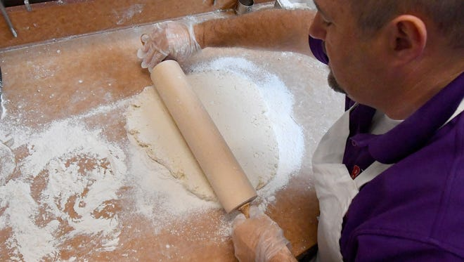 Dale Haywood, franchise director of operations, rolls the dough a specific way before cutting out the biscuits, placing them on a pan and moving them to the oven. Haywood demonstrates the art of making biscuits at the new Bojangles' on Richmond Road in Staunton on Wednesday, May 16, 2018. The restaurant opens this Saturday.