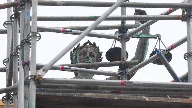 The statue of Lady of Justice on top of the Augusta County courthouse holds high her new set of scales, replaced on Wednesday, May 16, 2018. Augusta County contracted Doug Sheridan of Sunspots Studios to replace the scales. The statue remains surrounded by scaffolding as roof work continues to the building.