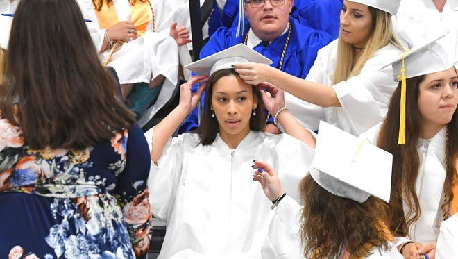 Graduate Jayden Beasley receives a help in adjusting her hat after she slides into place for Fort Defiance High School's Class of 2018 group photo before the start of their commencement ceremony at Eastern Mennonite University on Tuesday, May 22, 2018.