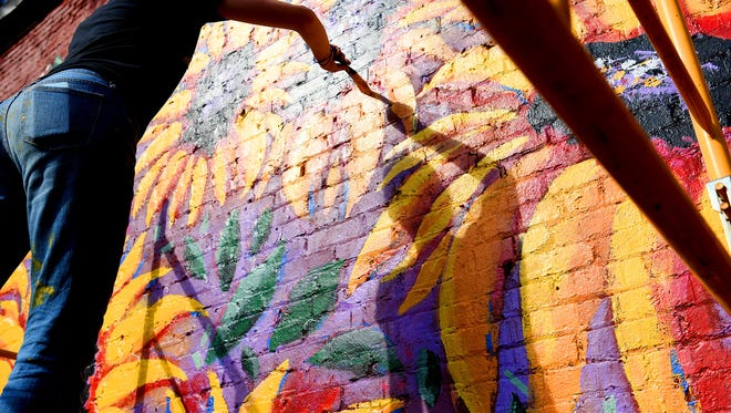 The sun casts her shadow as Madeline Maas, a homeschool graduate from Waynesboro, adds detail to a sunflower mural she paints on the wall of a building on Greenville Avenue in downtown Staunton near the giant watering can on Friday, July 27, 2018.