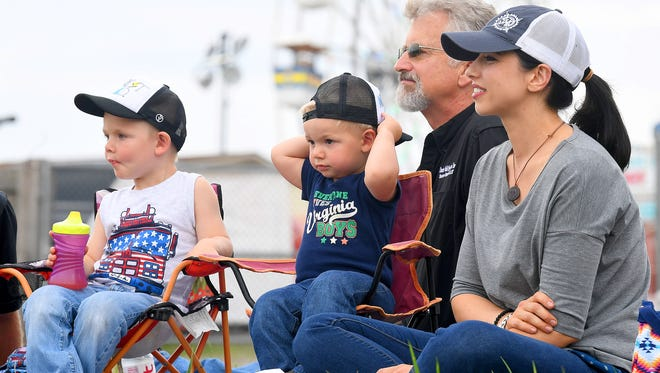 Brothers Stillman Davis, 3, and Langston Davis, 1, sit together next to grandfather Kevin Traylor and mother Brittany Davis. They watch motocross at the Augusta County Fair on Tuesday, July 31, 2018.