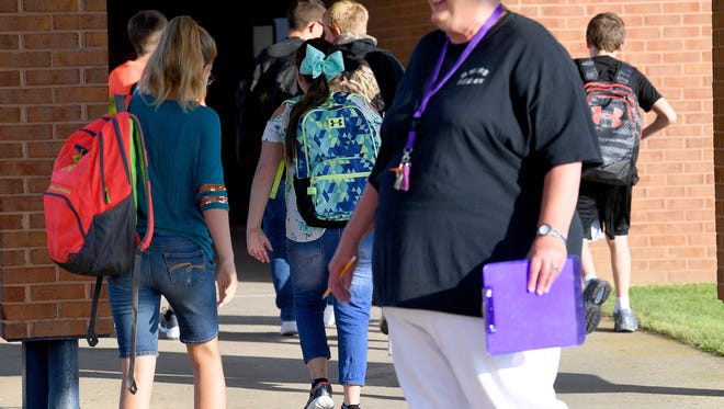 Students make the walk from the buses to the building, passing a smiling teacher along the way. They arrive for the first day of the new school year at Beverley Manor Middle School on Tuesday, August 7, 2018.