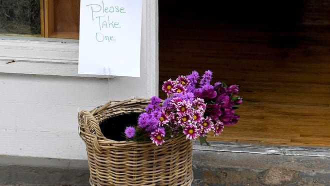 Flowers in a basket just outside the door of Hedge Fine Bllooms are free for visitors take on the Downtown Mall in Charlottesville, Va., on Saturday, August 11, 2018.