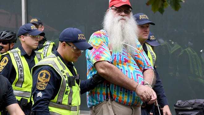 A man is arrested by the Virginia State Police outside a CVS pharmacy on the Downtown Mall in Charlottesville, Va., on Saturday, August 11, 2018.