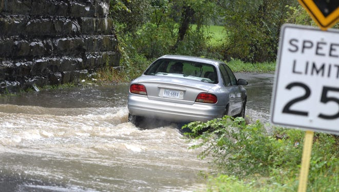 A car drives through the high water on Desper Hollow Road near the intersection with Route 250 in Brands Flat Monday.