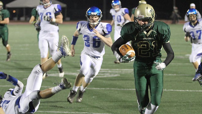 Oshkosh North's Jared Dittmer (21) runs the ball along the sideline to the end zone on a reception against  West Friday.