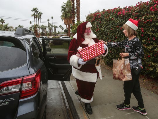 Bob Elias, the director of social services and Meals on Wheels for the Joslyn Center, dressed as Santa with a gift of a disaster preparedness kit and volunteer Karen Burke, make their Meals on Wheels food delivery run on Thursday, December 22, 2016 in Palm Desert.