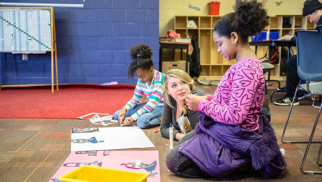 UNC Asheville student Brooke Johnson, center, helps youngsters at the YWCA with their Martin Luther King Jr. posters. One hundred forty UNC Asheville students participated in a variety of service projects to mark Martin Luther King Jr. Day on Jan. 18.