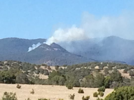 A plume of smoke is seen Sunday afternoon after the Sisters Fire was sparked in the Gila National Forest.