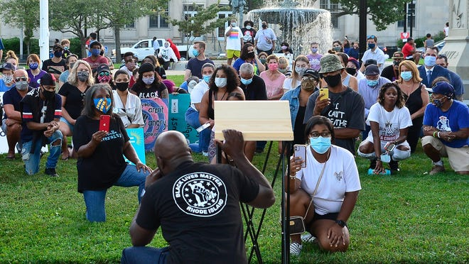 A Rhode Island Black Lives Matter supporters take a knee during Friday night's peaceful protest held at the Taunton Green on August 28, 2020.