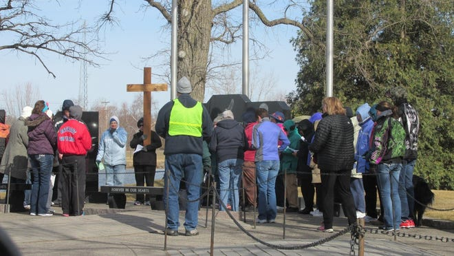 Participants on the Silent Walk for Peace stopped to pray at a number of sites in Little Falls, including St. Gabriel's Hospital, Morrison County Jail and Government Center, Bank Square, Mississippi River bridge and dam, Maple Island Park, Shelly Funeral Service and First United Church. Shown here, the group pauses for prayer and song at the Veteran's Memorial.