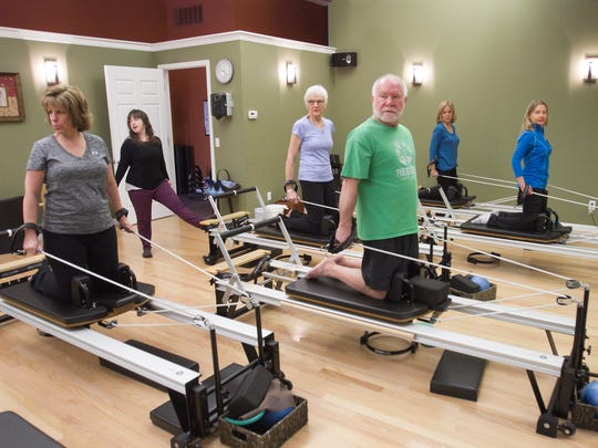 "Pilates instructor Rebecca Gushue, second from left, directs a work out on specialized Pilates machines in a ""group reformer"" class with students, from left, Mary Hale, Jane Pendleton, Jeff Sobolsewski and Sally Belian and Into Motion studio director Cherie Boschma."