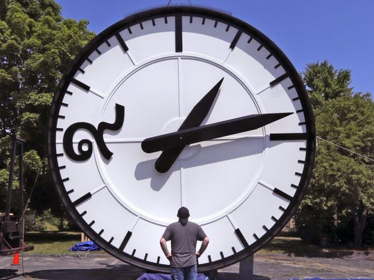 """In this Thursday, July 25, 2019 photo, workers at the Electric Time Company in Medfield, Mass., test a 20 foot high clock, built for the a new train station in Bangkok, Thailand, prior to packing and shipment. The clock features a """"9"""" in Thai number script. Daylight saving time ends at 2 a.m. local time Sunday, Nov. 3, 2019, when clocks are set back one hour. Losing an hour of daylight sounds like a gloomy preview for the dark winter months, and at least one study found an increase in people seeking help for depression after turning the clocks back to standard time in November _ in Scandinavia. But far more research says that the springtime start of daylight saving time may be more harmful, linking it with more car accidents, heart attacks in vulnerable people and other health problems that may persist throughout the time change. (AP Photo/Charles Krupa)"""