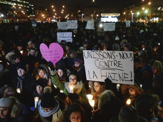 People attend a vigil in Montreal on Monday for victims of Sunday's shooting at a Quebec City mosque.