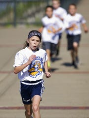 Karoline Bachelder, 10, lengthens her lead during the 'Wildcat Mile' race in Downtown Newburgh, Ind., Monday morning. Bachelder beat everyone at the school in the one mile race and will run for Castle South Middle School as a sixth-grader next year.