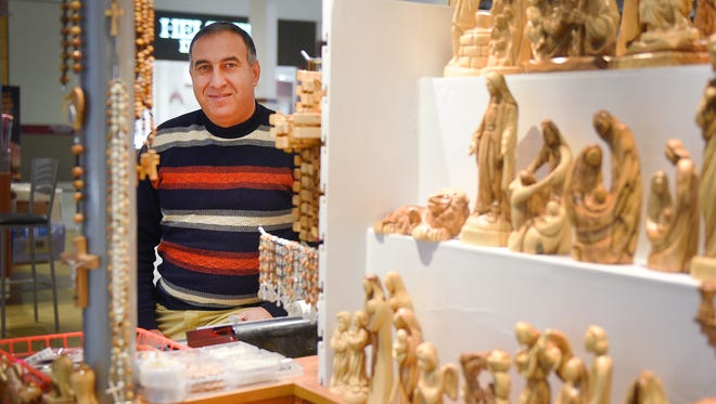 Bishara Salsa talks about the woodcarvings he brought from Bethlehem to the Empire Mall for the Christmas season Tuesday, Nov. 21, at his kiosk in the mall.