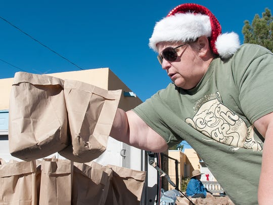 Kumie Wise helps load luminarias on a truck Monday.
