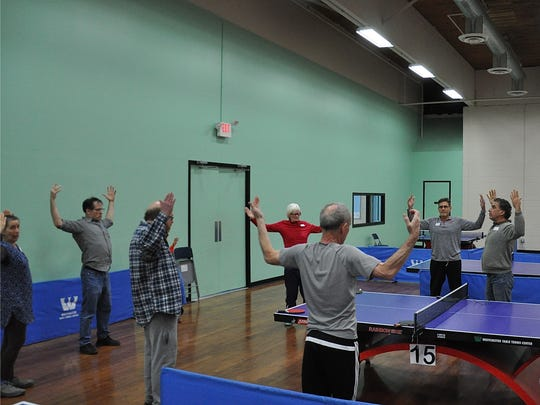 Gary Tacon (r), a yoga instructor from Nyack, leads stretching exercises before Parkinson's ping-pong night..