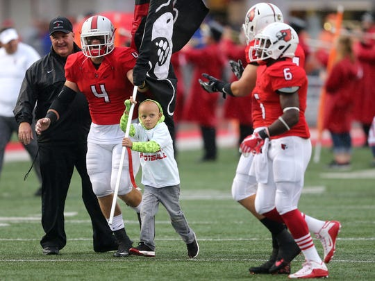 Walter Herbert, 6, leads the Colerain Cardinals on the field before the high football game between the St. Xavier Bombers and the Colerain Cardinals, Friday, Sept. 1, 2017, at Colerain High School in Colerain Township.