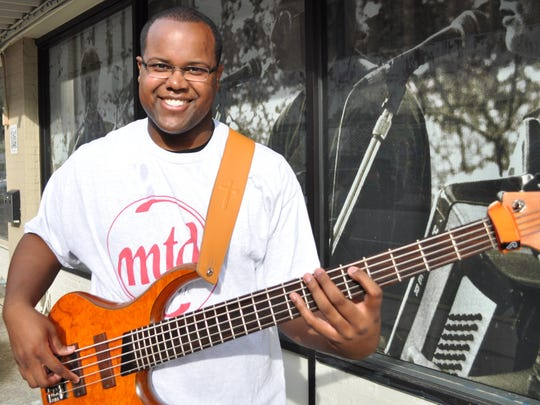 Antoine Stewart stands with his bass guitar outside of Tipitina's Music Co-op in downtown Alexandria, where he played his original music for a live audience for the first time in 2012.