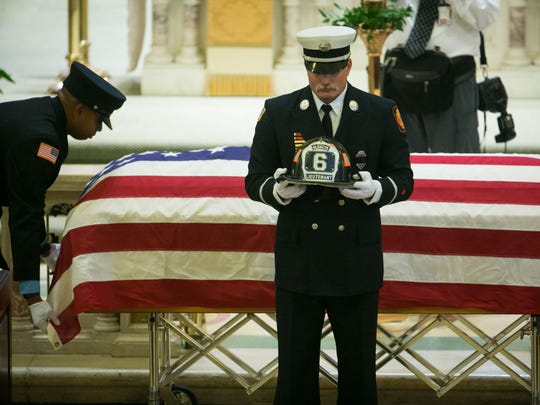 The helmet of Lt. Christopher Leach is removed from