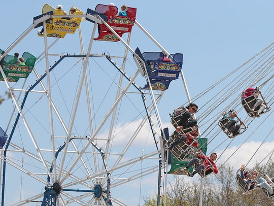 Visitors ride the Ferris wheel and swing ride at Bay