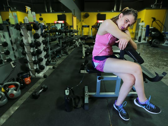 Dima Azzam rests in between sets of exercises during a workout.