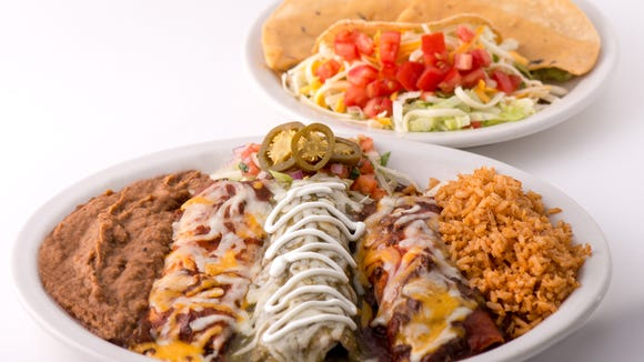 The Elvis Presley memorial combo at Chuy's consists of a beef Tex-Mex enchilada, a cheese Ranchero enchilada, a chicken-tomatillo enchilada, a seasoned ground sirloin crispy taco, homemade tostada chips dipped in chile con queso,  Mexican rice and refried beans.