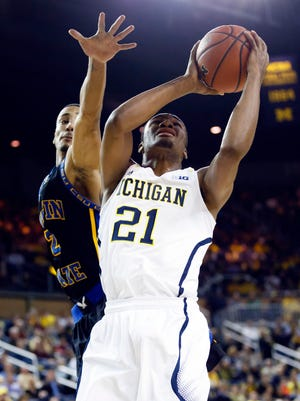 Michigan guard Zak Irvin (21) rises to shoot against Coppin State's Sterling Smith.