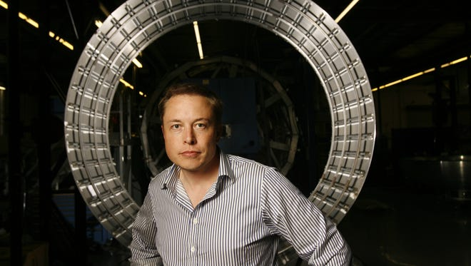 Elon Musk stands in front of parts of the first stage of the Falcon 9 rocket at the company's headquarters in El Segundo, Calif. on Sept. 18, 2007.