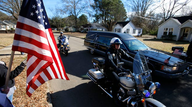 """A hearse carries the body of Tupelo, Miss.,  police Sgt. Kevin """"Gale"""" Stauffer on Dec. 27."""