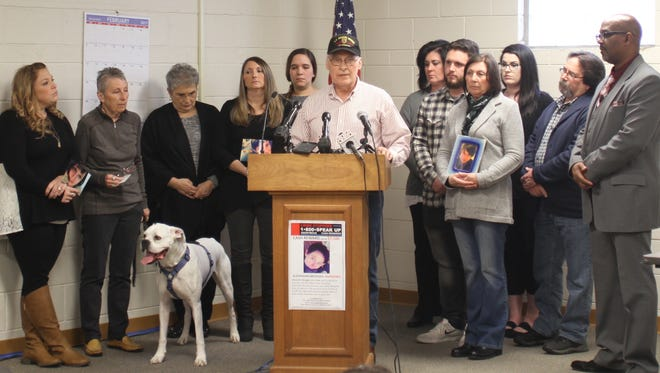 Franz Brueger, the father of Alexandra Brueger, surrounded by other family members at a press conference held Tuesday in Rose Township in partnership with Crime Stoppers of Michigan to ask for the public's help in solving the 31-year-old woman's July 30 murder.