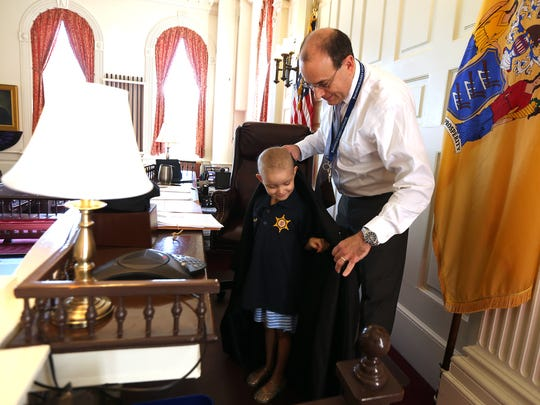 Judge Stuart Minkowitz places his robes onto 6-year-old Juliet Nigara of Mountain Lakes as she is honored at the Morris County courthouse by the Morris County Sheriff's Office as their 'Hero for a Day.' August 26, 2016, Morristown, NJ