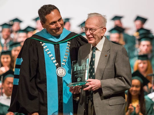 Headmaster Dr. Michael Marinelli presents Donn Devine with the Alumnus of the Year Award during graduation ceremonies at Archmere Academy in 2015.