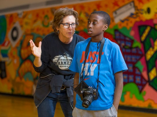 Volunteer Robyn Wishna, a Brooktondale photographer and Ithaca College instructor, works with M.J. Thomas as he works to photograph Ithaca Mayor Svante Myrick. Thomas, 11, is a sixth-grade student at Boynton Middle School.