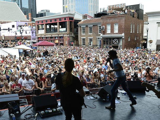 Chris Janson, right, performs at the Plaza stage during