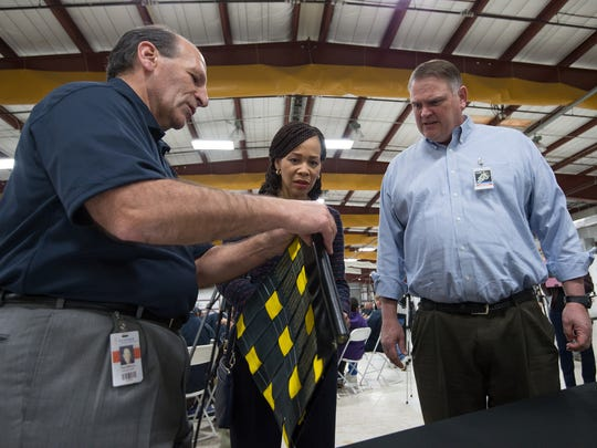 ILC Dover president and CEO Fran DiNuzzo shows U.S. Rep. Lisa Blunt Rochester and Delaware Sen. Colin Bonini one of the products manufactured at the Frederica plant during a tour of the facility in Nov. 2017.