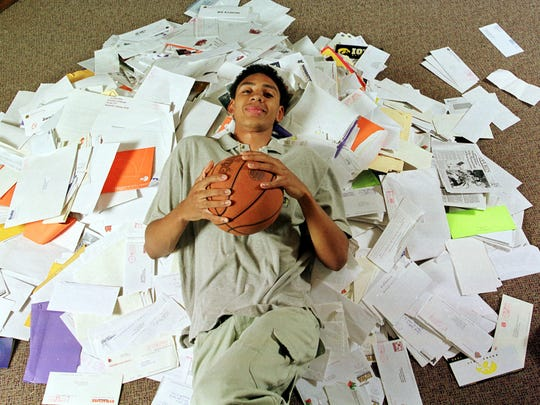 Bloomington North High School basketball player Jared Jeffries lays on top of the hundreds of letters he's received from colleges interested in his attention.