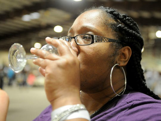 In this file photo, LaRei Roberts tastes a wine March 24 from 6th Street Winery at the Red River Wine and Beer Festival in the J.S. Bridwell Agricultural Center. A growing number of wineries and tasting rooms are popping up in downtown Wichita Falls and other parts of the county. The 6th Street Winery is set to receive $25,000 toward renovation of a historic warehouse downtown for a permanent location for production and a tasting room.