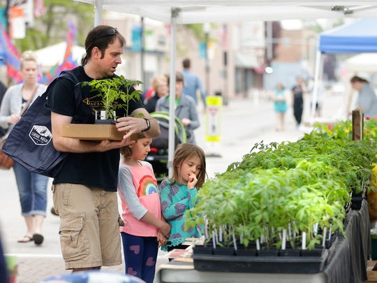 Andy Waisanen and his daughters, Lucy and Hattie of Fond du Lac, shop for plants Saturday May 19, 2018 at the Fond du Lac Farmers Market on Main Street in Downtown Fond du Lac. Doug Raflik/USA TODAY NETWORK-Wisconsin