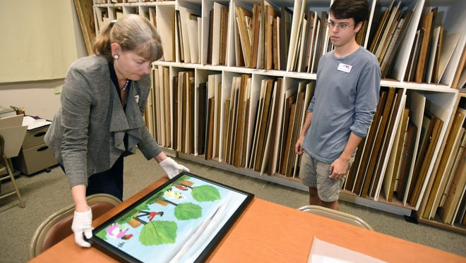 Dr. Lisa Nicoletti lays out a painting by Clementine Hunter for student Ben Green to study at Centenary College's Meadows Museum of Art.