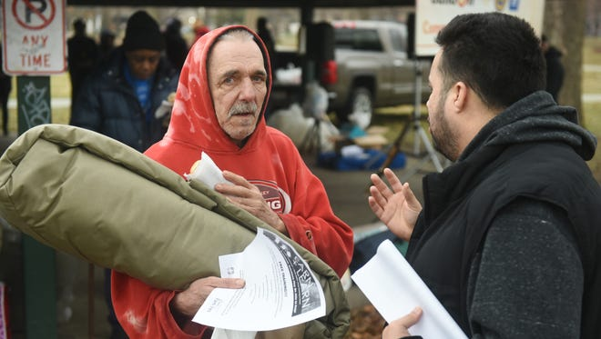 Emanuel Hernandez, right, of The Southwest Economic Solutions, assists a homeless man as the UAW-GM Center For Human Resources and buildOn students address issues of homelessness through community service at Clark Park  in Detroit on Saturday March 25, 2017.